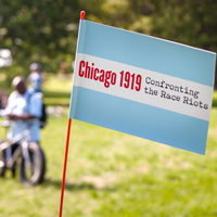 Chicago_1919_Confronting_the_Race_Riots_Flag_In_Foreground_With_Blurry_Cyclists_And_Green_Landscape_In_Background