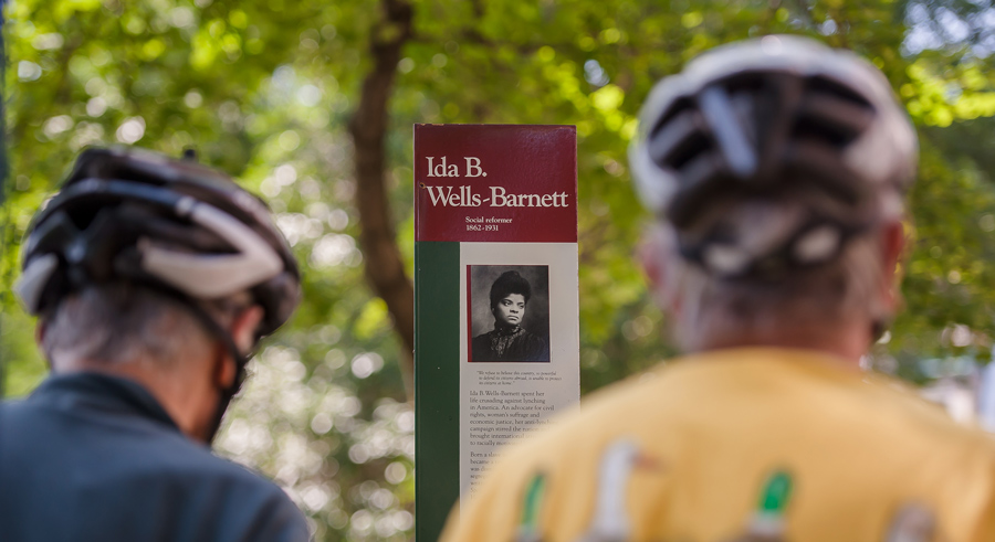 Two_Cyclists_Looking_At_Sign_With_Bio_Of_Ida_B._Wells-Barnett