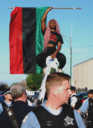 BlackWomanOnLadderHoldingUpFlagWithPoliceOfficerInForeground