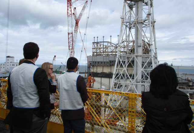 Group_Of_People_Looking_At_Damaged_Nuclear_Reactor_In_Fukushima_Daiichi