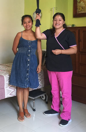 Young_Mexican_Midwife_Standing_Near_Bed_With_Young_Pregnant_Mexican_Woman