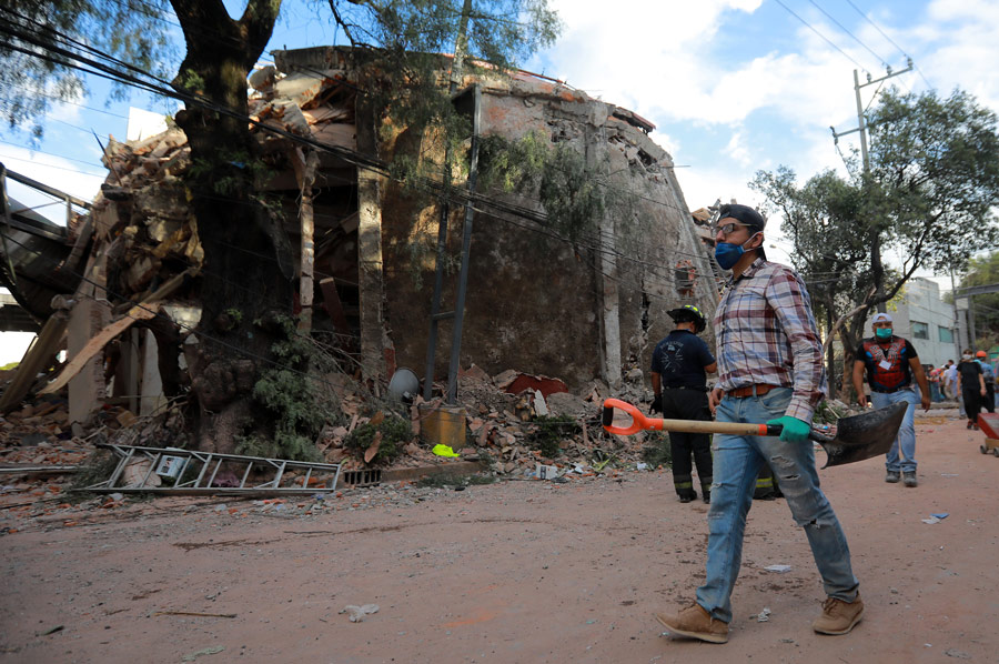 Man_With_Shovel_Walking_Down_Street_With_Collapsed_Buildings_And_Rubble