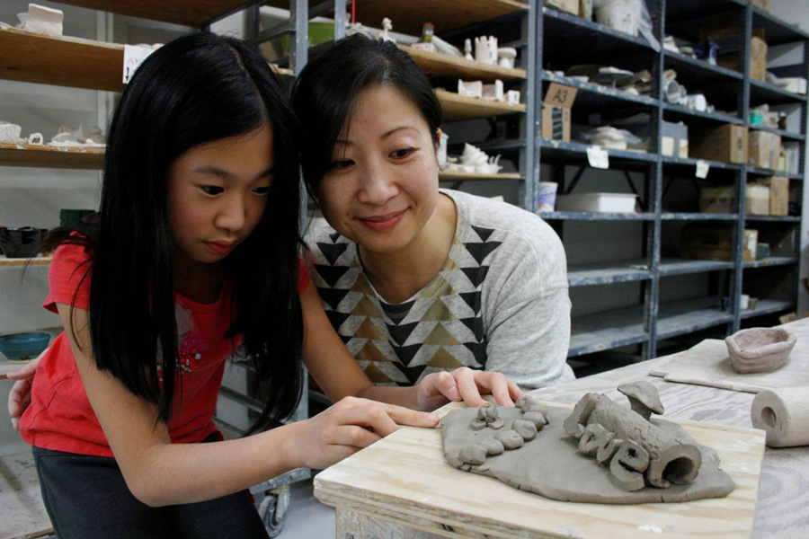 Asian_Mother_And_Daughter_Looking_At_Clay_Project_In_Art_Studio