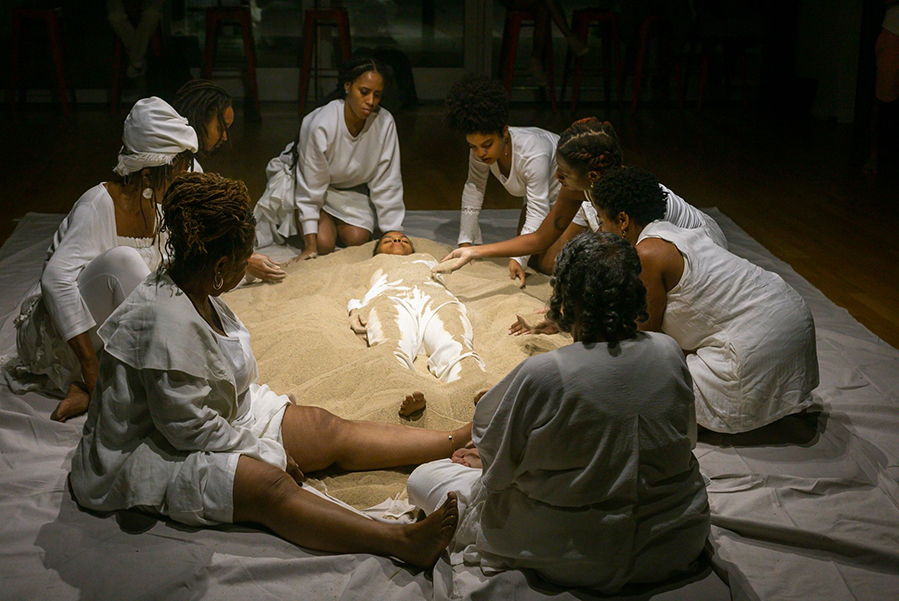 Group_Of_Black_Performers_Wearing_White_Clothing_Scooping_Sand_Onto_A_Woman_Lying_On_The_Floor