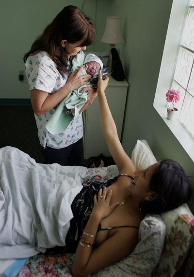 Latinamotherandmidwifeholdingnewbornbaby