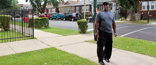 AfricanAmericanmanwalkingalongneighborhoodsidewalk