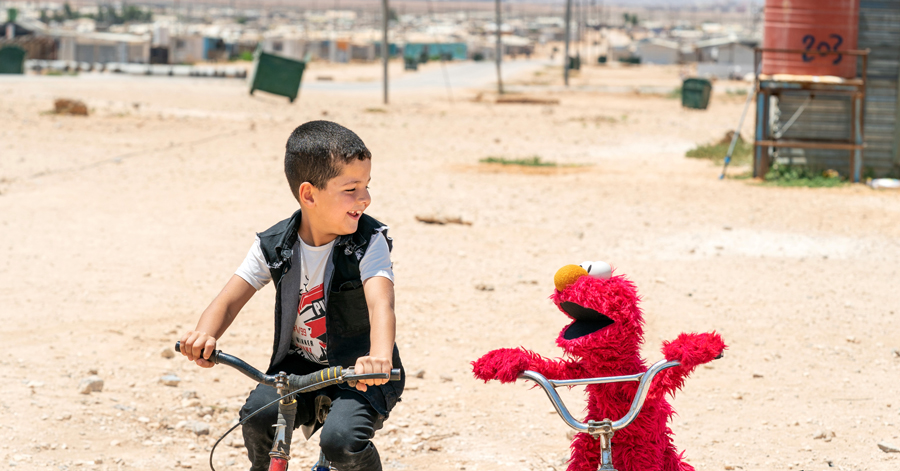 Boy_On_Bicycle_Next_To_Red_Muppet_On_Bicycle