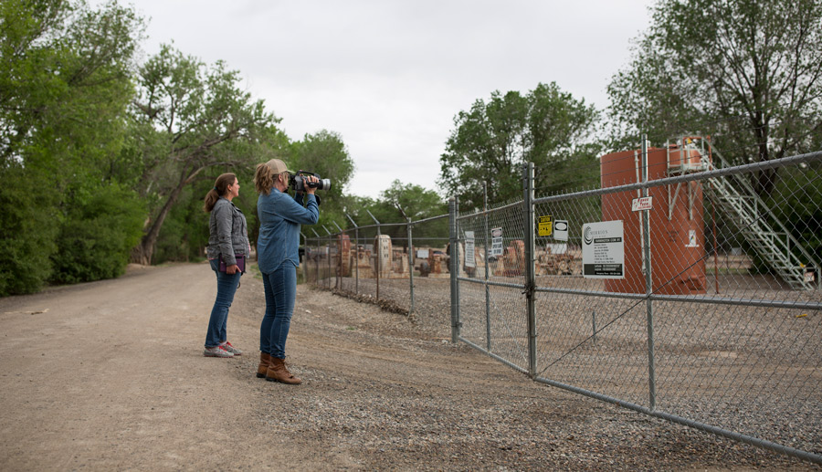 Two_Women_Using_Infrared_Camera_Outside_Fenced_Area_With_Oil_Well